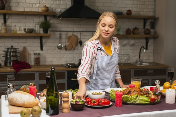 Long shot of woman arranging food in the kitchen