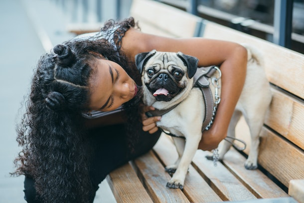 A woman kisses her pug while sitting on a park bench in the city during the holidays.