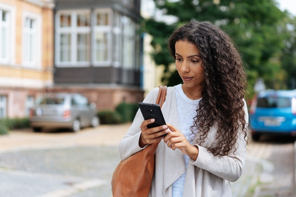 Young woman looking at phone at a text from someone who ghosted her