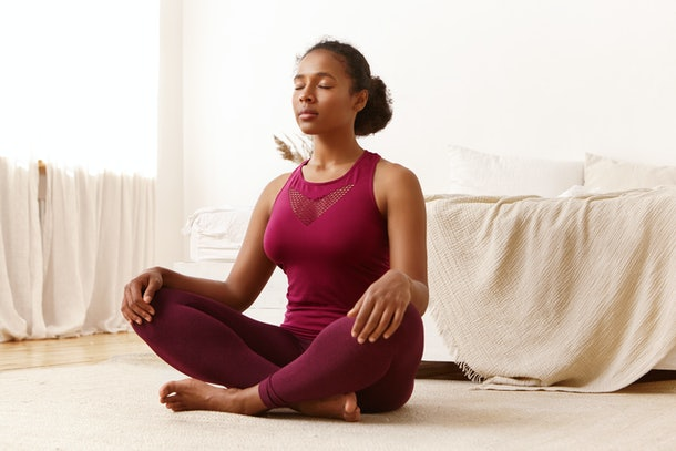 Health, active lifestyle, well being and people concept. Portrait of attractive peaceful young black dark-skinned female in stylish sports clothes meditating indoors, keeping her eyes closed