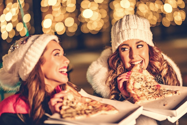 Two women enjoy date night outside and laugh with slices of pizza in their hands.