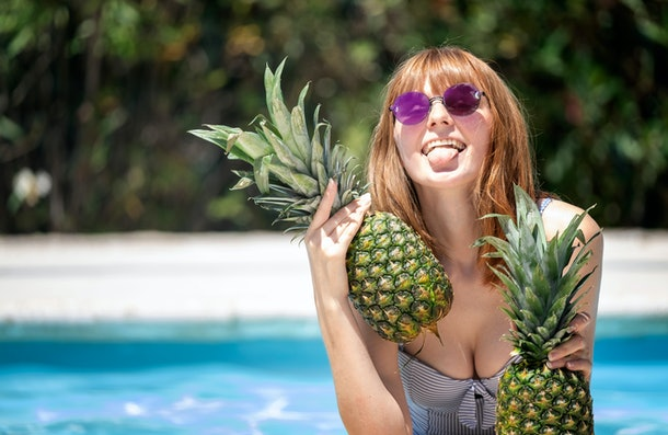 Caucasian girl with sunglasses holding two pineapples in a pool