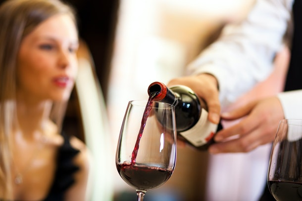 Waiter pouring red wine to a woman