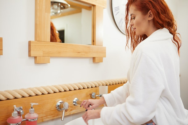 Red-haired woman turns on the sink in the bathroom.