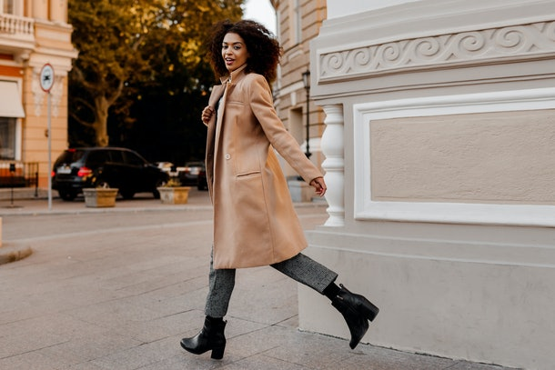 A chic city woman walks down the sidewalk in a tan pea coat, black pants, and black boots.
