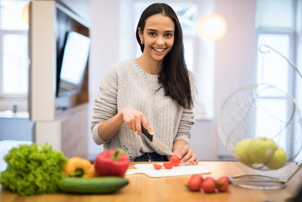 The young woman cuts vegetables in the kitchen with a knife and laptop on the table. Vegetable Salad. Diet. Dieting Concept. Healthy Lifestyle. Cooking At Home. Prepare Food. With place for text