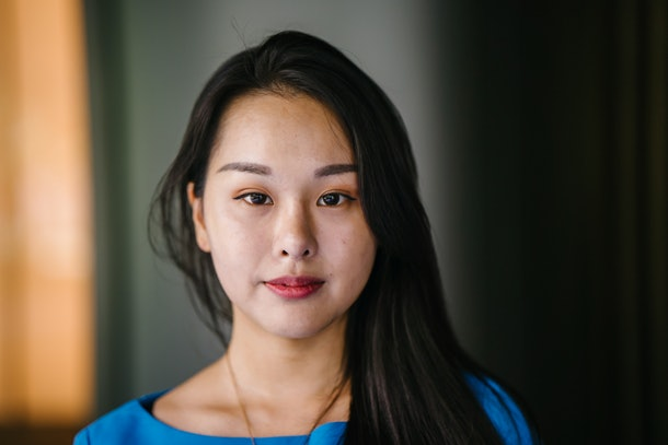 Portrait of a young and attractive Asian Korean woman in a blue top and black dress against a gold metal background. She is smiling softly and exudes confidence, class and elegance.