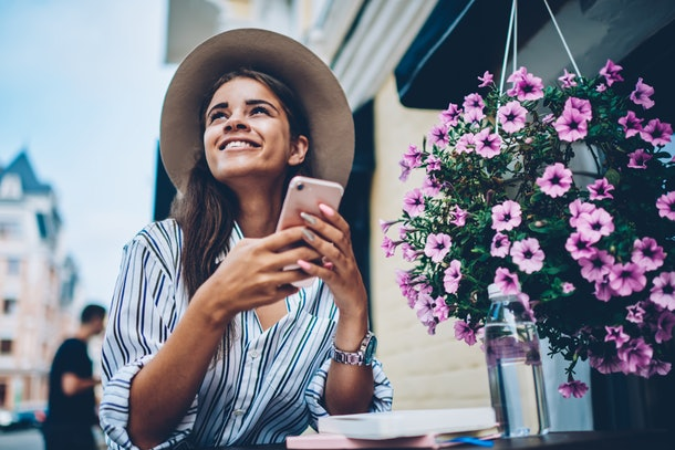 Cheerful dreamy stylish student wearing cool hat and looking up while received notification with good news on smartphone.Positive female sending sms resting in coffee shop outdoors in modern downtown