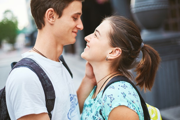Young people, couple having date on the street. A loving couple on a date on a summer evening. The guy with the girl hugs and kisses. Youth, first feelings, first love, first dates. faces close up