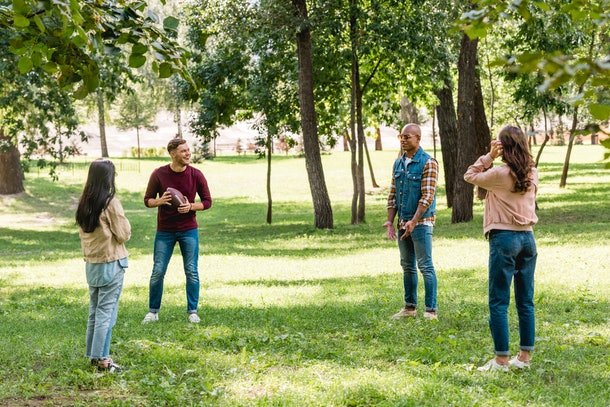 A group of four friends playing football in the park on a sunny day.