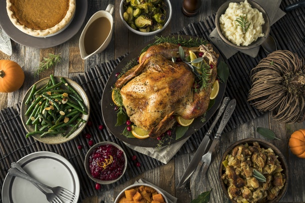 A Thanksgiving turkey is in the middle of a dinner table, surrounded by stuffing, cranberry sauce, and other side dishes.