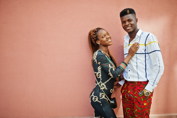 Handsome stylish african american couple posed at street together in love against pink wall.