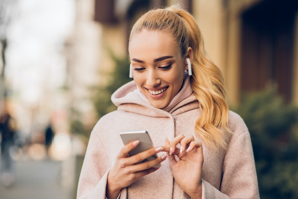 Happy woman texting outdoors on city street, listening music in airpods