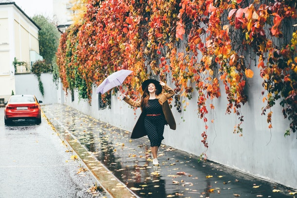 Young happy emotional girl laughing and jumping with umbrella on colored autumn street. Woman with umbrella walking in autumn city. Beautiful fall time in nature.