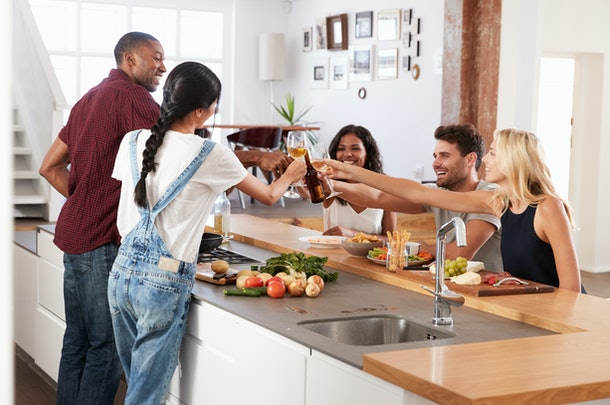 A group of friends gather around island in kitchen preparing dinner and toasting their wine glasses and beer.