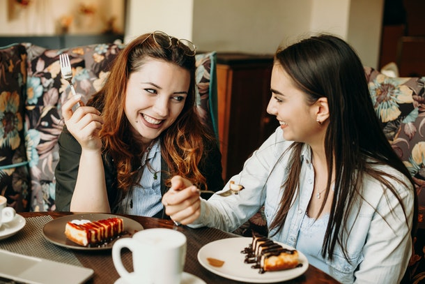 Two amazing caucasian woman sitting in a coffee shop smiling having fun while eating a cake and drinking coffee.