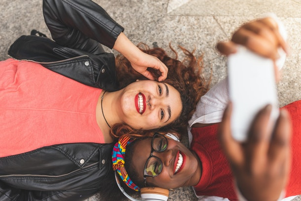 Two friends smile while posing for a selfie on the floor.