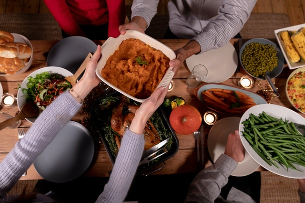 A group of friends sit around the dinner table and pass the side dishes to each other on Thanksgiving.