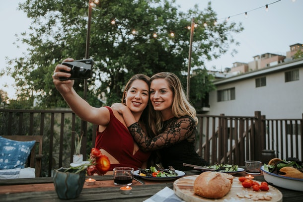 A couple takes a selfie on a camera while eating Thanksgiving dinner outside.