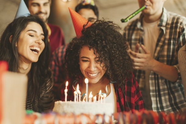 A woman with a party hat on is surrounded by her friends and smiles at her birthday cake.