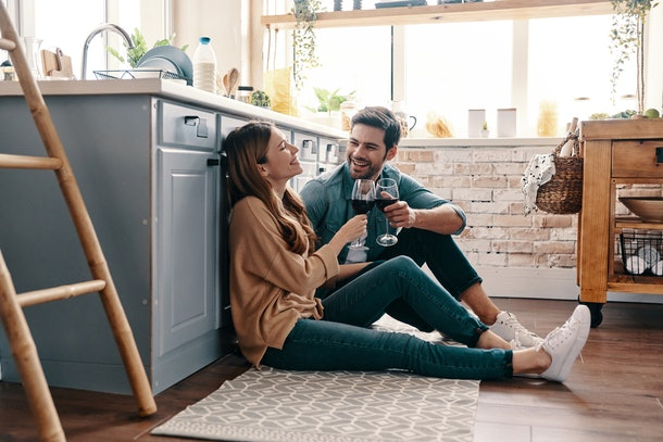 A happy couple toast their wine glasses on the kitchen floor.