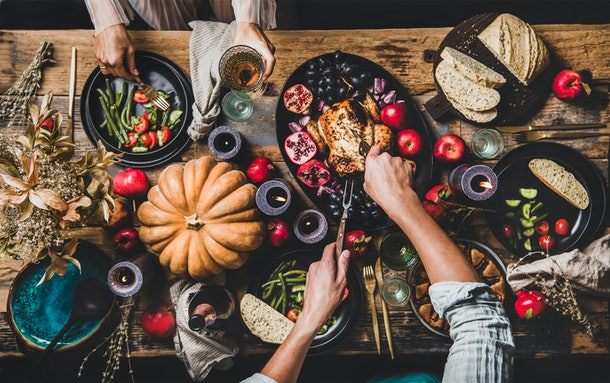 A couple dishes out food onto their plates from a colorful and festive Thanksgiving spread.