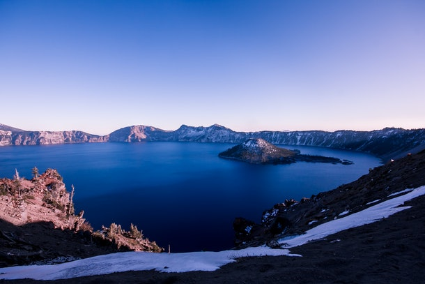 A winter sunset in Crater Lake National Park in Oregon turns the sky blue, purple, and yellow.