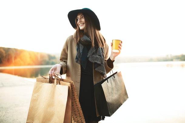 Attractive cute girl in with the shopping bags and warm drink in her hand