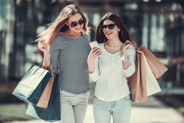 Beautiful girls in sun glasses are holding shopping bags, using a smart phone and smiling while standing outdoors