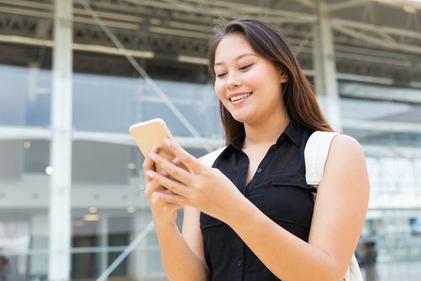 Positive female student texting message on cell. Young mix raced woman standing outside, using mobile phone, looking at screen, smiling. Digital technology concept