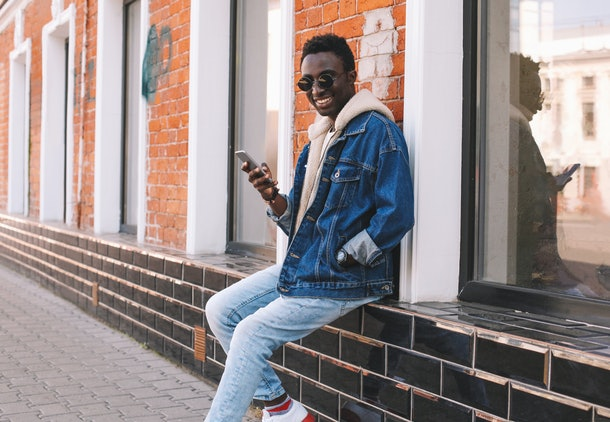 Happy cool smiling african man with smartphone sitting on city street over brick wall background