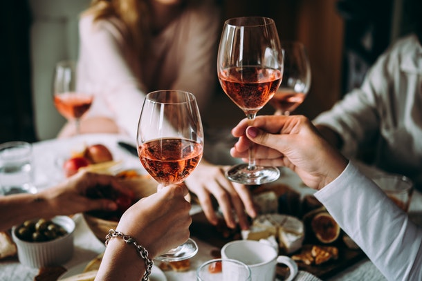 Two girls hold up their glasses of rosé during a Friendsgiving dinner.