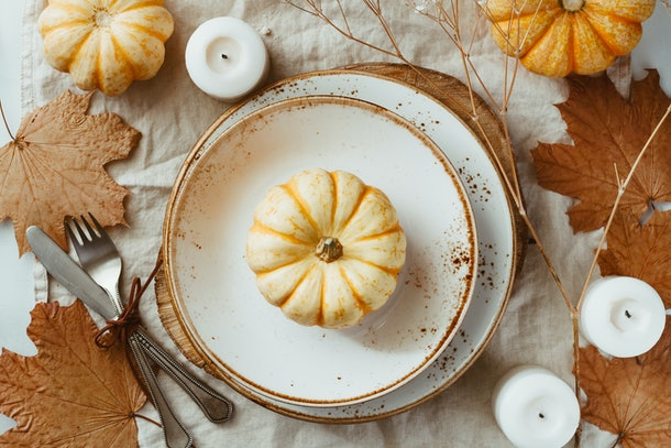 A fall place setting includes white and brown decorated plates, leaves, candles, and pumpkins.