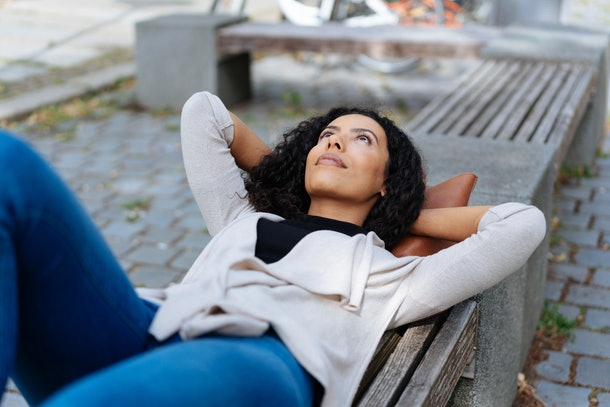 Young woman lying on a bench in an urban park or street daydreaming with her hands behind her head staring up into the sky