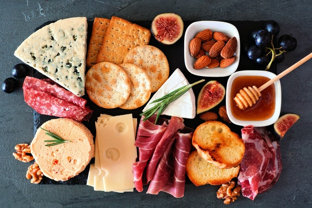 A colorful cheese board includes multiple kinds of meats, cheeses, and fruits.