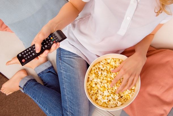 Close up of woman eating popcorn with remote control tv.