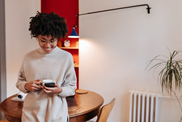 Dark-skinned lady in long sweater smiles, drinks tea and chats in smartphone