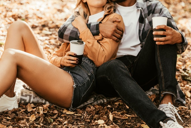 A couple sits on a blanket in fall foliage and drinks coffee on Thanksgiving.