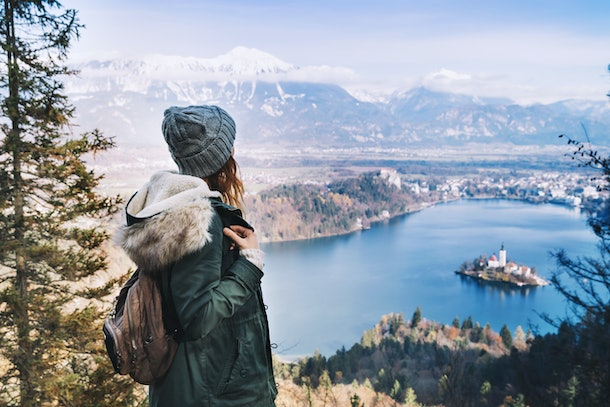 Hiking young woman with alps mountains and alpine lake on background. Travel Slovenia, Europe. Top view on Island with Catholic Church in Bled Lake with Castle and Mountains in Background.