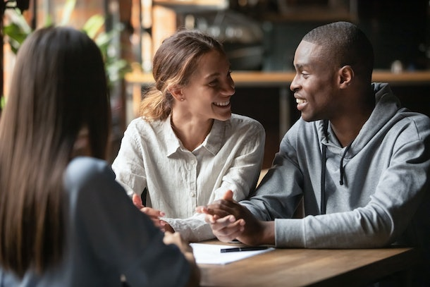African man and mixed race woman couple feel happy great offer opportunity people looking at each other sitting in cafe with real estate agent female sign contract, client and service provider concept