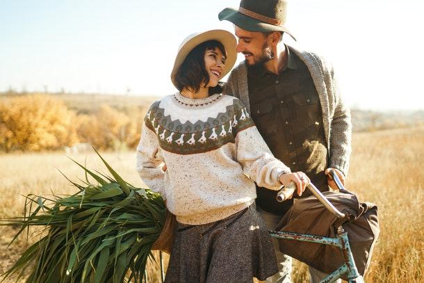 A stylish couple poses with a bicycle and a bag of fresh produce in a field on Thanksgiving.