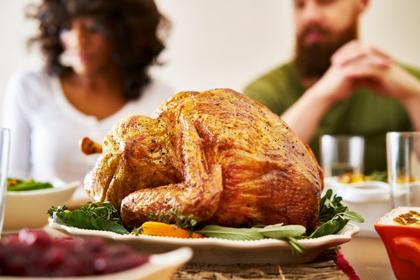 Two people sit behind a turkey platter at a table before they enjoy Thanksgiving dinner.