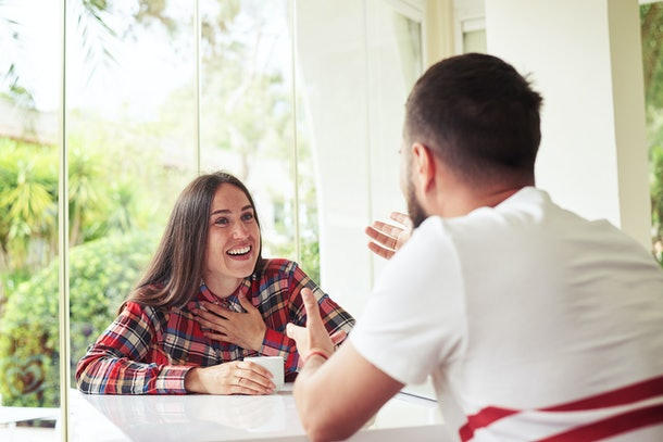 Young man and woman are sitting in bright sunlit room with garden view and vigorously discussing something
