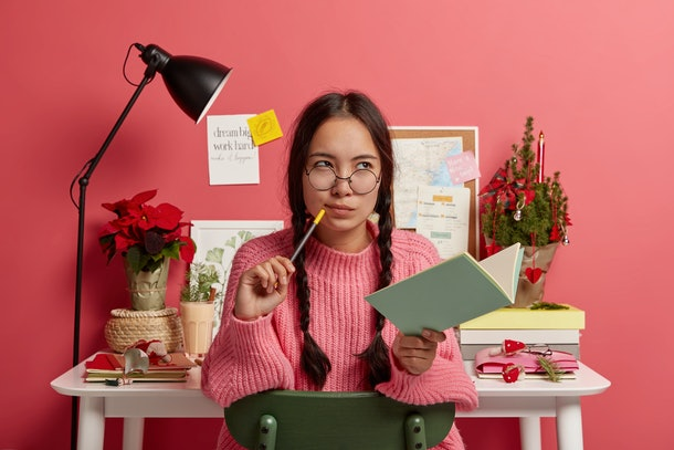 Serious contemplating Asian girl with combed plaits, holds notebook and pencil, writes down future plans and goals for coming New Year holidays, poses with own diary in study room over rosy wall