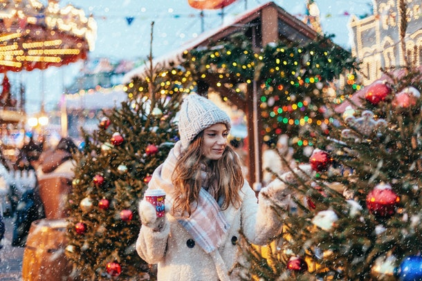 Girl drinking hot coffee while walking in Christmas market decorated with holiday lights in the evening. Feeling happy in big city. Spending winter vacations in Red square, Moscow, Russia.
