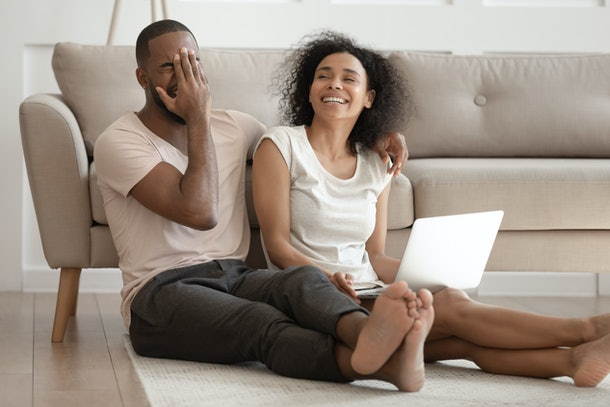 Young overjoyed happy african american family couple sitting on floor mat with computer on knees at living room, laughing at joke, having fun, watching comedian movie or remember positive stories.
