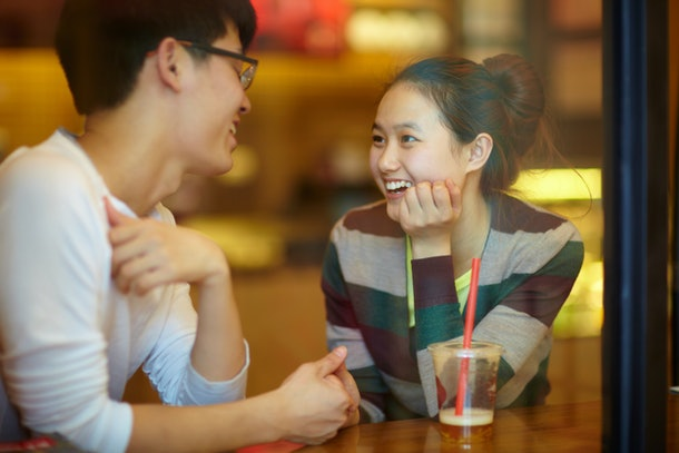 young man and young asian woman dating in cafe