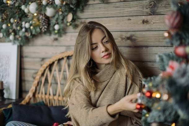 A woman sits next to a Christmas tree in her home while hanging an ornament.