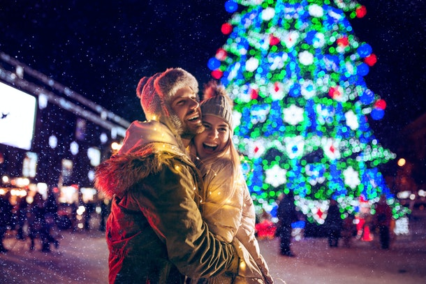 A couple enjoys a fun holiday date outside, hugging in front of a Christmas tree that is all lit up.