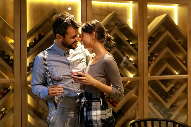 A happy couple on a holiday date taste different wines in a wine cellar.
